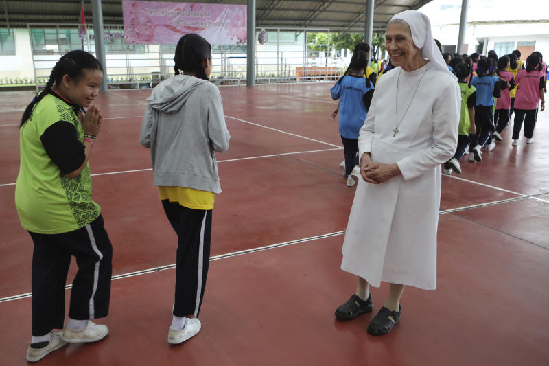 """In this Aug. 27, 2019, photo, Thai students give a Thai traditional greeting gesture of """"wai"""" to ST. Mary's School Vice Principal Sister Ana Rosa Sivori, right, as they go back to classroom at the girls' school in Udon Thani, about 570 kilometers (355 miles) northeast of Bangkok, Thailand. Sister Ana Rosa Sivori, originally from Buenos Aires in Argentina, shares a great-grandfather with Jorge Mario Bergoglio, who, six years ago, became Pope Francis. So, she and the pontiff are second cousins. (AP Photo/Sakchai Lalit)"""