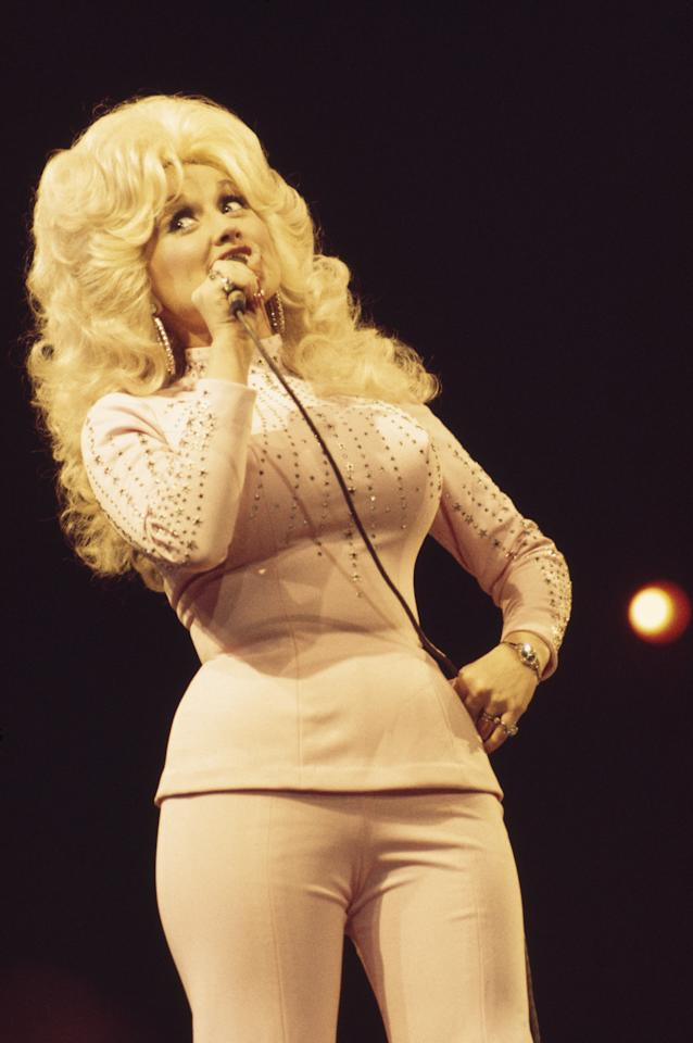 Dolly Parton singing into a microphone during a live concert performance at the Wembley Empire Pool, London, England, Great Britain, in April 1976.