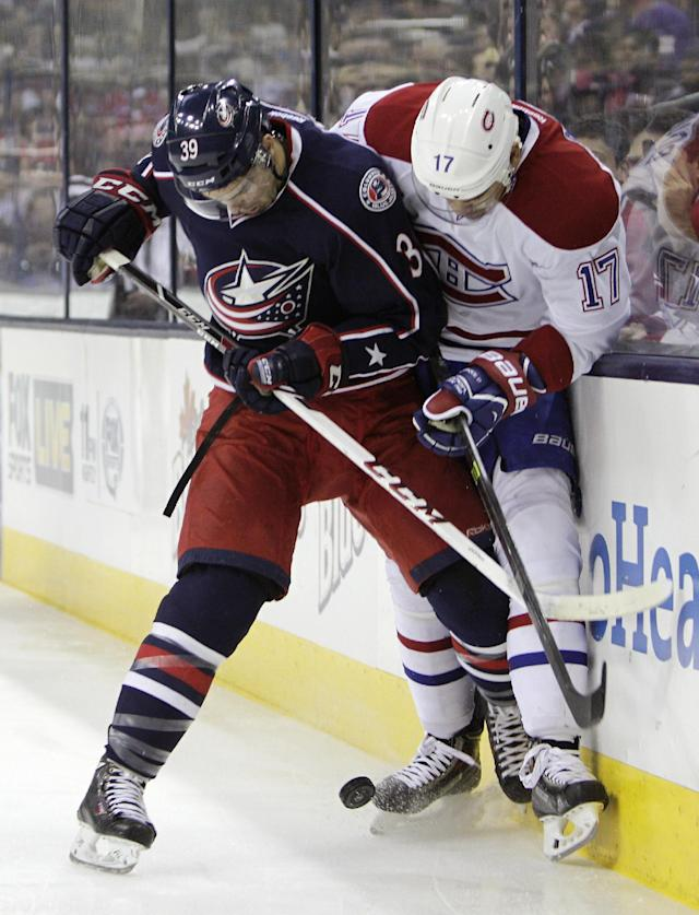 Columbus Blue Jackets' Michael Chaput, left, and Montreal Canadiens' Rene Bourque fight for a loose puck during the first period of an NHL hockey game Friday, Nov. 15, 2013, in Columbus, Ohio. (AP Photo/Jay LaPrete)