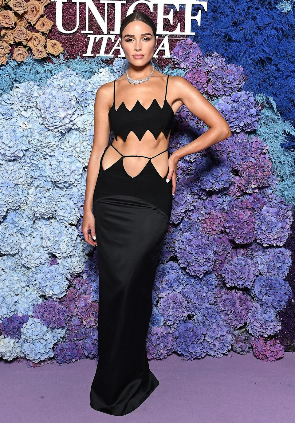 <p>in a black gown featuring a crop top and cutout detailing at the waist. </p>