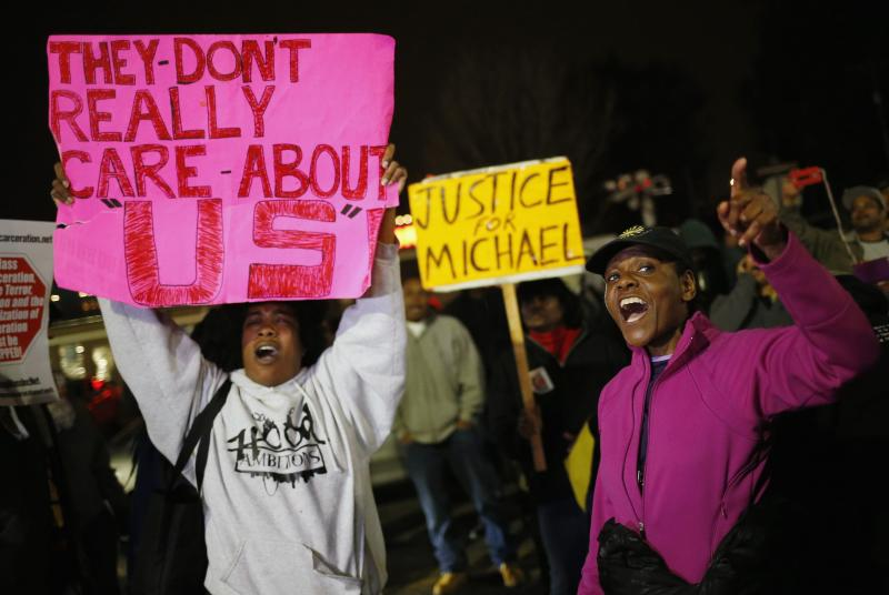 Protesters demonstrate across the street from the Ferguson Police Department in Ferguson