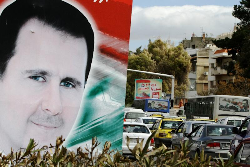 A banner bearing a portrait of Syrian President Bashar al-Assad stands next to a street in the city of Damascus, March 4, 2015 (AFP Photo/Louai Beshara)
