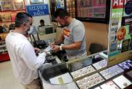 Gold dealer Gunay Gunes talks to a customer who wants to buy gold, in Istanbul