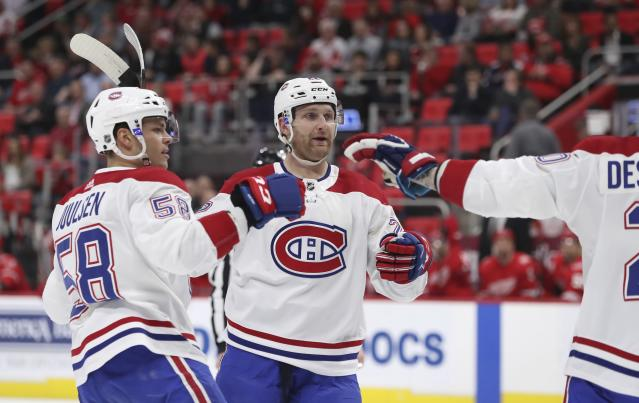Montreal Canadiens defensemen Noah Juulsen (58) and Karl Alzner, center, congratulate teammate Nicolas Deslauriers, right, after his goal during the first period of an NHL hockey game against the Detroit Red Wings, Thursday, April 5, 2018, in Detroit. (AP Photo/Carlos Osorio)