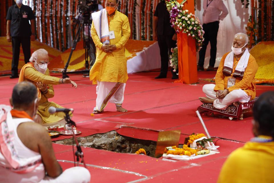 Indian Prime Minister Narendra Modi performs the groundbreaking ceremony of a temple dedicated to the Hindu god Ram, watched by Rashtriya Swayamsevak Sangh (RSS) chief Mohan Bhagwat, seated right, in Ayodhya, India, Wednesday, Aug. 5, 2020. The coronavirus is restricting a large crowd, but Hindus were joyful before Prime Minister Narendra Modi breaks ground Wednesday on a long-awaited temple of their most revered god Ram at the site of a demolished 16th century mosque in northern India. (AP Photo/Rajesh Kumar Singh)