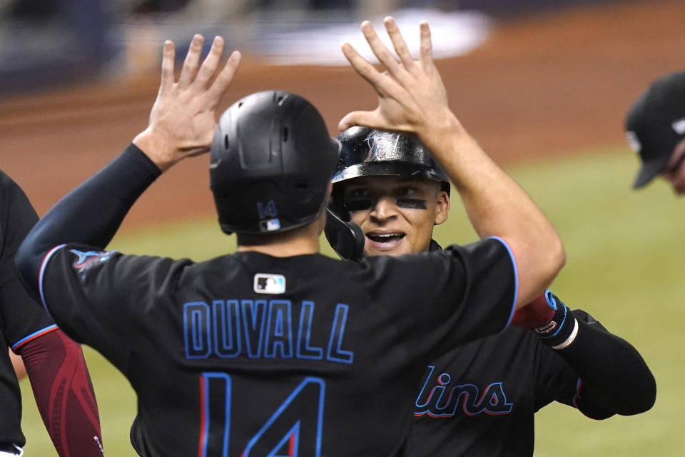 Miami Marlins' Isan Diaz, right, is met by Adam Duvall (14) at the plate after hitting a grand slam during the third inning of a baseball game against the Milwaukee Brewers, Friday, May 7, 2021, in Miami. (AP Photo/Lynne Sladky)