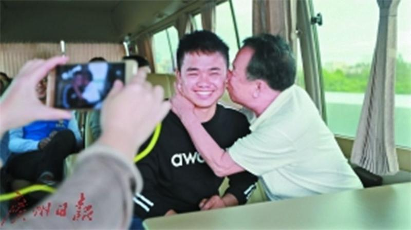 Li Risheng smiles as his biological father kisses him on the cheek when they were reunited. Source: Guangzhou Daily
