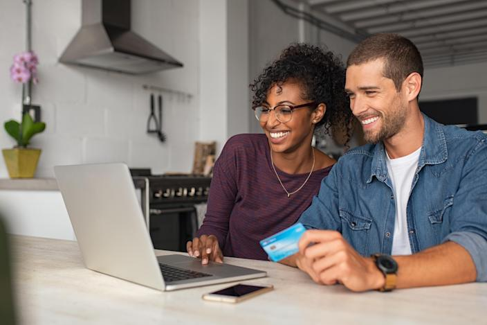 Smiling young couple making shopping online with credit card and laptop at home. Happy multiethnic couple holding debit card while buying on ecommerce site using laptop. Cheerful guy and african girl making online purchase.
