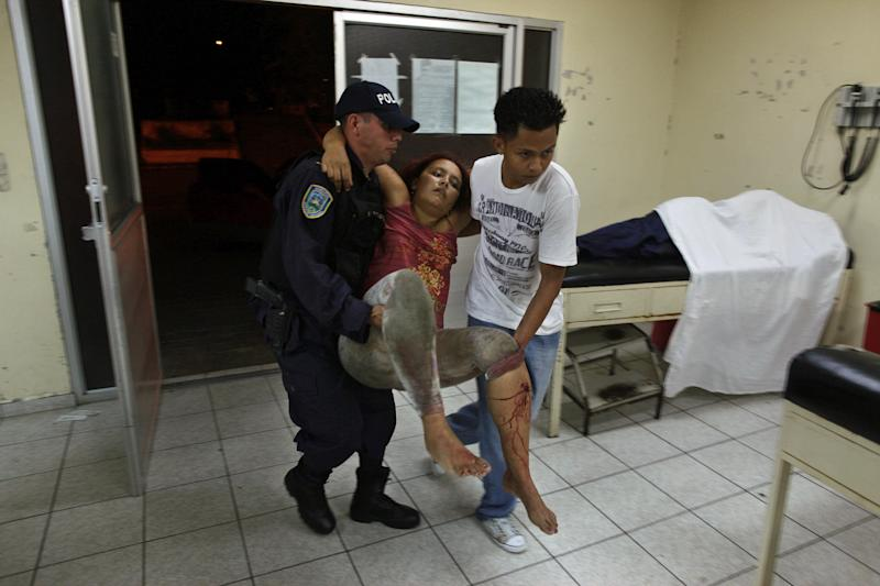 FILE - In this March 11, 2012 file photo, a woman who was injured during a shooting at a pool hall is carried into the Catalino Rivas Public Hospital in San Pedro Sula, Honduras. In Honduras, you never know where danger lurks and it's not hard to become a fatality. (AP Photo/Esteban Felix, File)