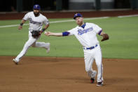 Texas Rangers third baseman Todd Frazier throws to first to complete the ground out by San Diego Padres' Manny Machado as Isiah Kiner-Falefa, rear, looks on in the seventh inning of a baseball game in Arlington, Texas, Monday Aug. 17, 2020. (AP Photo/Tony Gutierrez)