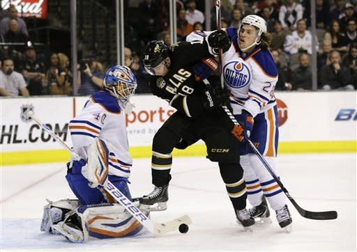 Dallas Stars' Reilly Smith (18) is unsuccessful at scoring as Edmonton Oilers' Devan Dubnyk (40) stops the shot with help from Ryan Jones (28) in the first period of an NHL hockey game on Thursday, Feb. 28, 2013, in Dallas. (AP Photo/Tony Gutierrez)