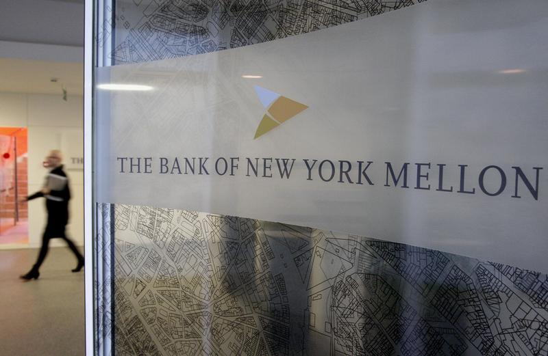 A woman walks past a logo at the office of the Bank of New York Mellon in Brussels