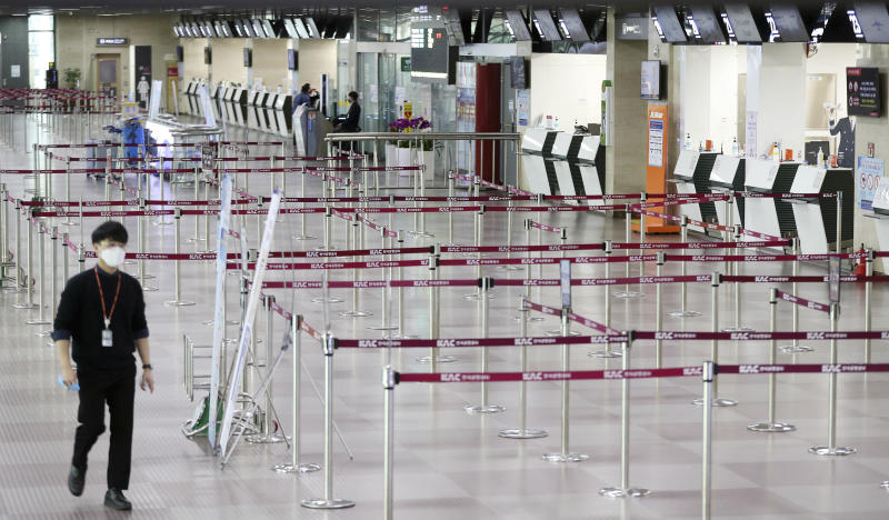 """A man wearing a face mask passes by empty ticket counters at the Daegu Airport in Daegu, South Korea, Monday, Feb. 24, 2020. South Korea reported another large jump in new virus cases Monday a day after the the president called for """"unprecedented, powerful"""" steps to combat the outbreak that is increasingly confounding attempts to stop the spread. (KimHyun-tae/Yonhap via AP)"""