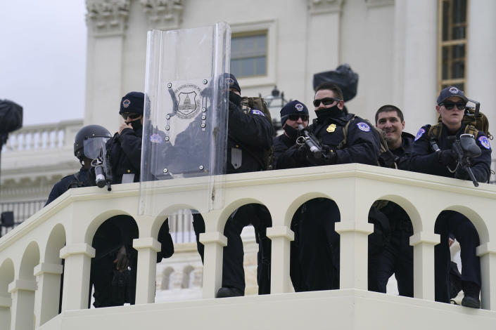 In this Wednesday, Jan. 6, 2021, photo, U.S. Capitol Police officer stand as violent rioters storm the Capitol, in Washington. The top watchdog for the U.S. Capitol Police will testify to Congress for the first time about the department's broad failures before and during the Jan. 6 insurrection. Among them was missed intelligence and old weapons that officers didn't feel comfortable using. (AP Photo/John Minchillo)