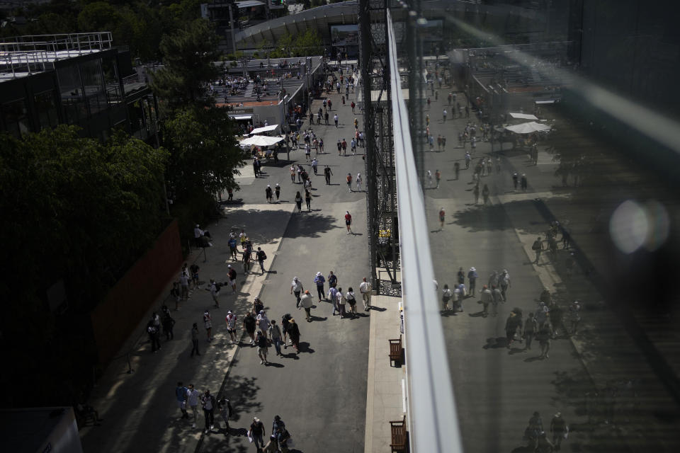 Spectators wander along the outside of the Court Philippe Chatrier on day three of the French Open tennis tournament at Roland Garros in Paris, France, Tuesday, June 1, 2021. (AP Photo/Christophe Ena)