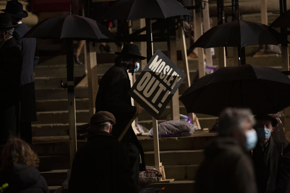A protester holds a sign on the steps of St Georges Hall. Peaky Blinders start filming in Liverpool, at St Georg's Hall, as season 6 gets underway, pictured in Liverpool city centre, March 4 2021. (SWNS)