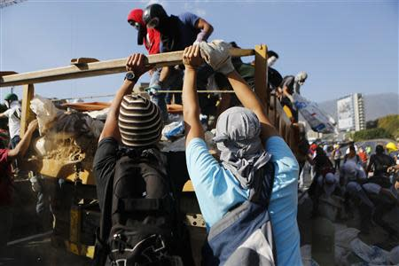 Anti-government protesters unload debris from a truck to build a barricade along a highway during a protest in Caracas