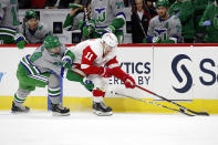Detroit Red Wings' Filip Zadina (11) tries to keep the puck away from Carolina Hurricanes' Jake Bean (24) during the first eriod of an NHL hockey game in Raleigh, N.C., Saturday, April 10, 2021. (AP Photo/Karl B DeBlaker)