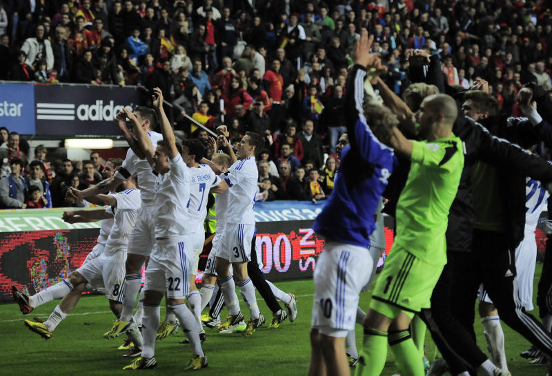 Finland's teammate celebrates with their fans after tied the match, 1-1 against Spain, during a Group I 2014 World Cup qualifying soccer match, at El Molinon stadium in Gijon, northern Spain, on Friday, March 22, 2013. (AP Photo/Alvaro Barrientos)