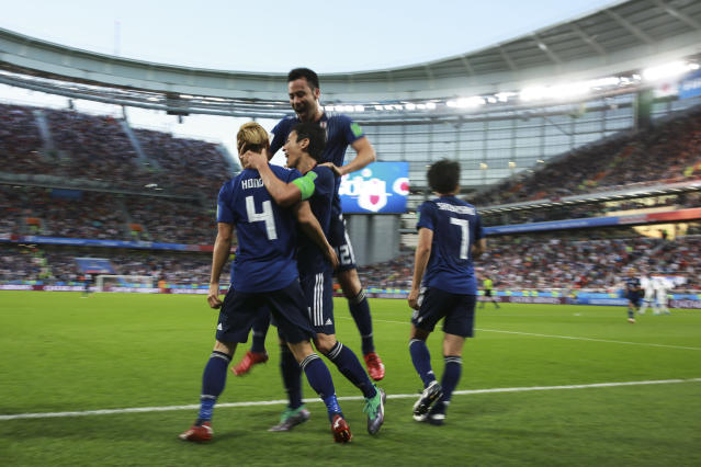 Japan's Keisuke Honda, left, celebrates with teammates after scoring his side's second goal during the group H match between Japan and Senegal at the 2018 soccer World Cup at the Yekaterinburg Arena in Yekaterinburg , Russia, Sunday, June 24, 2018. (AP Photo/Eugene Hoshiko)
