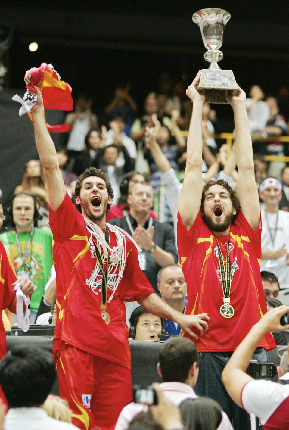 FILE - Spain's Pau Gasol, right, holds up the champion's trophy as teammate Rudy Fernandez waves a flag during ceremonies at the world basketball championships in Saitama, Japan, in this Sept. 3, 2006, file photo. Pau Gasol announced his retirement from basketball on Tuesday, Oct. 5, 2021, ending a career that lasted more than two decades and earned him two NBA titles and a world championship gold with Spain's national team. (AP Photo/Mark J. Terrill, File)