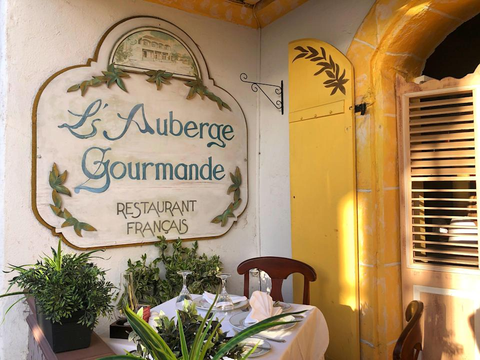 A sign reading L'Auberge Gourmande above a small table.