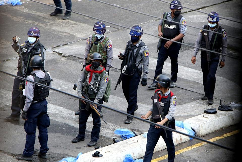 Armed officers in uniform and helmet stand on a street
