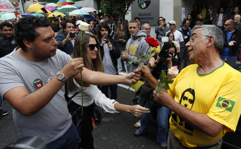 A supporter of Brazilian presidential candidate for the Workers Party (PT) Fernando Haddad (L) gives a rose to a supporter of far-right lawmaker and presidential candidate for the Social Liberal Party (PSL), Jair Bolsonaro, in Sao Paulo, Brazil during the second round of the presidential election, on October 28, 2018. - Brazilians will choose their president today during the second round of the national elections between the far-right firebrand Jair Bolsonaro and leftist Fernando Haddad (Photo by Miguel SCHINCARIOL / AFP) (Photo credit should read MIGUEL SCHINCARIOL/AFP via Getty Images)
