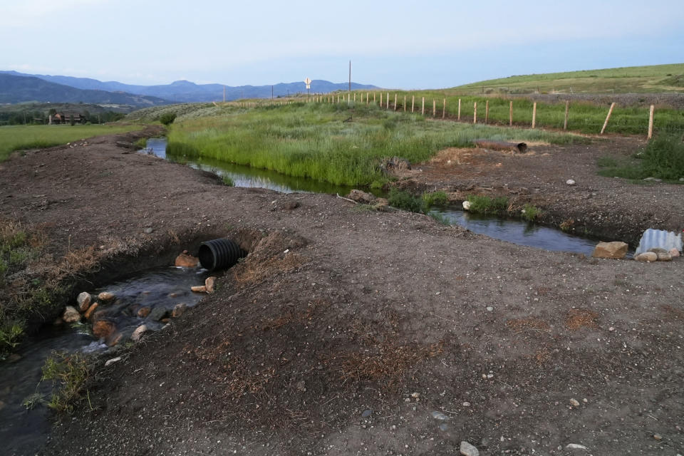 A pipe on the Stanko cattle ranch diverts water from the Woolery irrigation ditch, Tuesday, July 13, 2021, near Steamboat Springs, Colo. With the Yampa River approaching record low levels due to severe drought, ranchers are only able to use a third of their normal water supply, and Jim Stanko says if he can't harvest enough hay to feed his cattle, he may need to sell off some of his herd. (AP Photo/Brittany Peterson)
