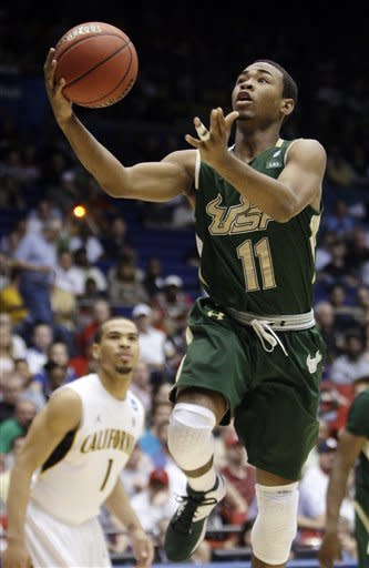 South Florida guard Anthony Collins (11) drives past California guard Justin Cobbs (1) in the first half of an NCAA tournament first-round college basketball game, Wednesday, March 14, 2012, in Dayton, Ohio. (AP Photo/Al Behrman)
