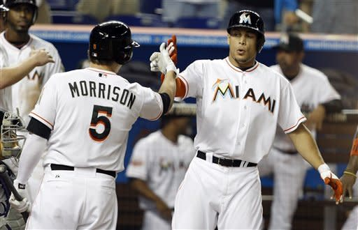 Miami Marlins' Giancarlo Stanton, right, is met at home plate by Logan Morrison (5) after hitting a grand slam in the fourth inning of a baseball game against the Colorado Rockies in Miami, Monday, May 21, 2012. (AP Photo/Lynne Sladky)