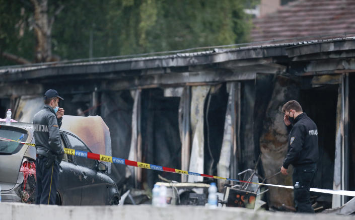 Police officers and forensics investigate the site at a burned out makeshift hospital after a fire in North Macedonia's northwestern city of Tetovo, early Thursday, Sept. 9, 2021. The blaze occurred late Wednesday at the makeshift hospital for COVID-19 patients. (AP Photo/Visar Kryeziu)