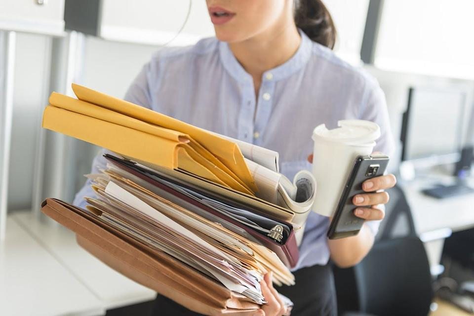Woman carrying coffee, phone and stack of papers