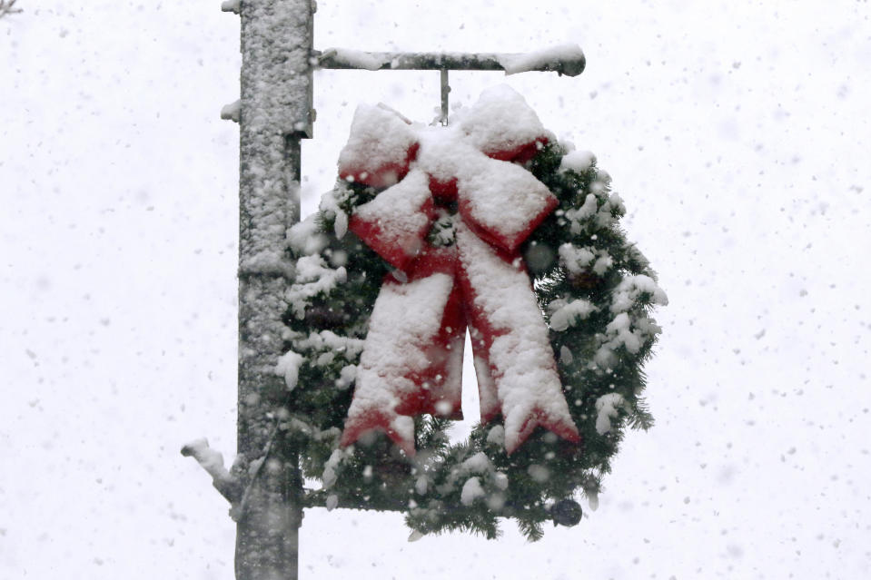 Snow clings to a holiday wreath, Saturday, Dec. 5, 2020, in downtown Marlborough, Mass. The northeastern United States is seeing the first big snowstorm of the season. (AP Photo/Bill Sikes)