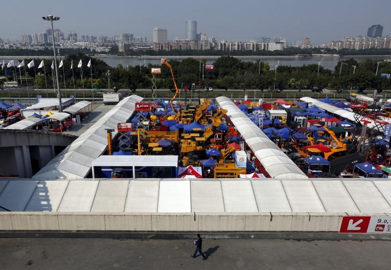 Man walks past construction vehicles on display at Canton Fair in the southern Chinese city of Guangzhou