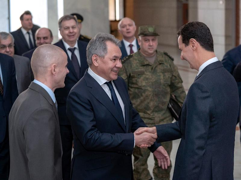 A handout picture released by the official Syrian Arab News Agency on March 19, 2019 shows Syrian President Bashar al-Assad greeting the visiting Russian defence minister, Sergei Shoigu, in Damascus