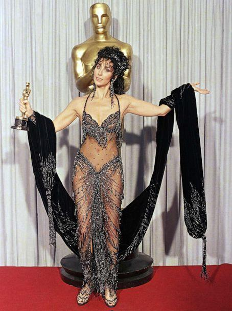 PHOTO: Cher shows off both her Oscar and Bob Mackie black-sequined gown after winning the award for best actress for her role as the superstitious young widow of 'Moonstruck' at the 60th Annual Academy Awards, April 12, 1988 in Los Angeles. (Lennox Mclendon/AP, FILE)
