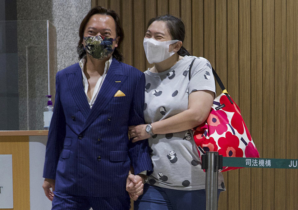 Lawrence Lau, left, one of the 47 pro-democracy activists charged with conspiracy, leaves with his relative after being released on bail outside a court after released in Hong Kong, Friday, March 5, 2021. Four of the 47 pro-democracy activists charged with conspiracy to commit subversion were released on bail Friday, after prosecutors dropped an appeal against the court's decision to grant them bail. (AP Photo/Vincent Yu)