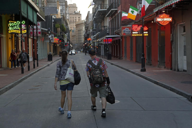 People walk down a nearly empty Bourbon Street, usually bustling with tourists and revelers, in the French Quarter of New Orleans, Thursday, March 19, 2020. Louisiana Governor John Bel Edwards and New Orleans Mayor Latoya Cantrell have ordered all restaurants and bars to close except for takeout, and asked residents to remain home and maintain social distancing from others when outside, due to the COVID-19 virus pandemic. (AP Photo/Gerald Herbert)