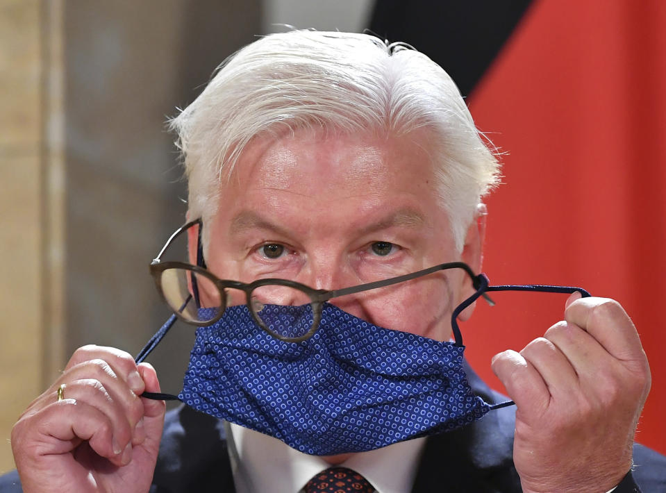 German President Frank-Walter Steinmeier struggles with his glasses and face mask as he attends a press conference after visiting the Salzburg Festival in Salzburg, Austria, Saturday, Aug. 22, 2020. (AP Photo/Kerstin Joensson)