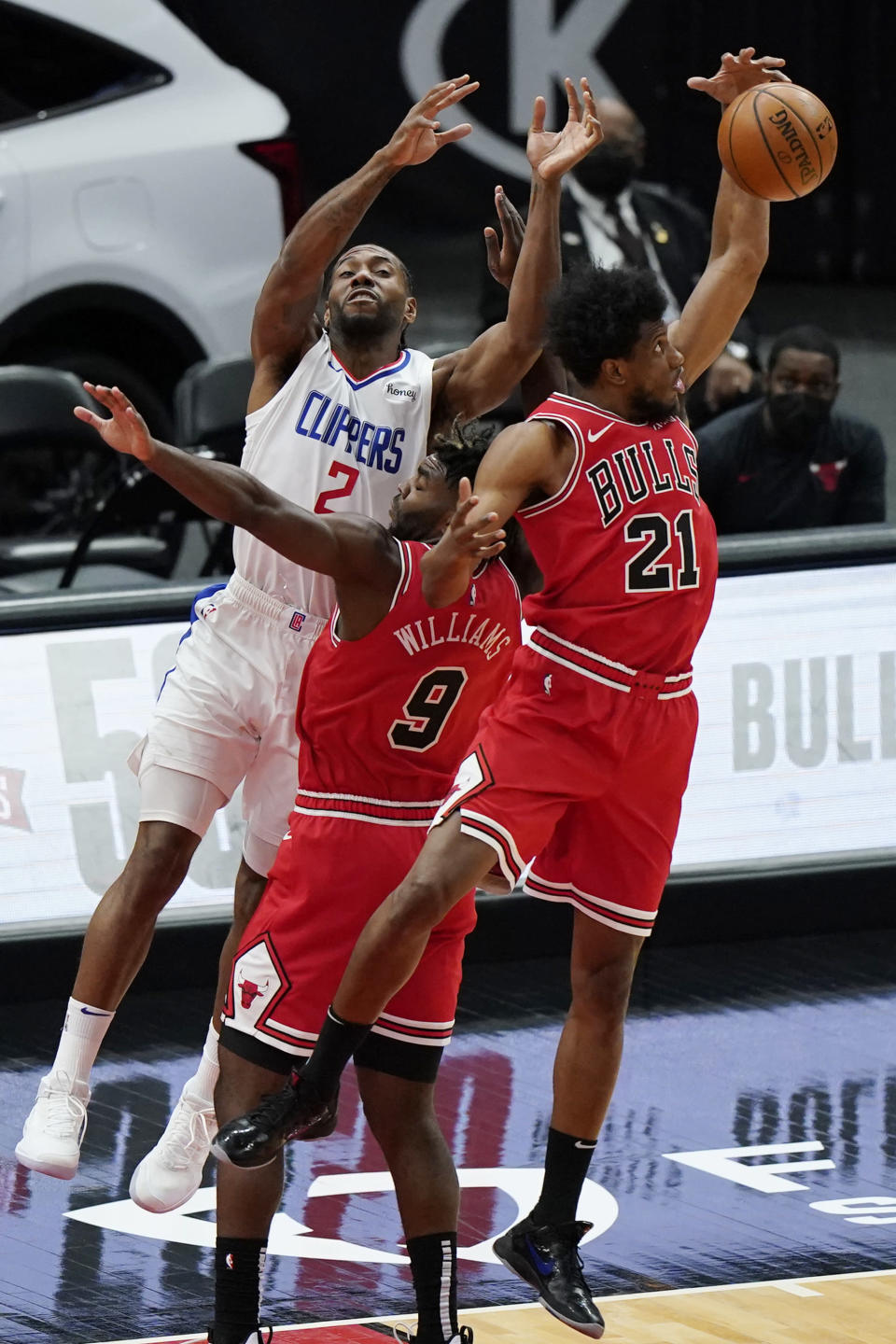 Chicago Bulls forward Thaddeus Young, right, intercepts a pass next to teammate Patrick Williams, center, and Los Angeles Clippers forward Kawhi Leonard during the first half of an NBA basketball game in Chicago, Friday, Feb. 12, 2021. (AP Photo/Nam Y. Huh)