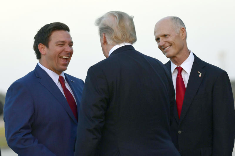 FILE- In this Oct. 31, 2018 file photo President Donald Trump, center, talks with Republican Gubernatorial candidate Ron DeSantis, left, and Florida Gov. Rick Scott, right, after arriving on Air Force in Fort Myers, Fla. Florida, the site of both a horrific school shooting and a monstrous killer hurricane in the last few months, has become the epicenter of the nation's polarizing political battles. (AP Photo/Susan Walsh, File)