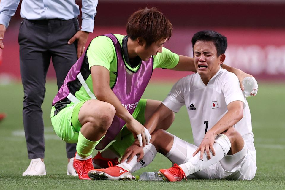 <p>Takefusa Kubo #7 of Team Japan looks dejected as he is consoled by Keisuke Osako #1 of Team Japan following defeat in the Men's Bronze Medal Match between Mexico and Japan on day fourteen of the Tokyo 2020 Olympic Games at Saitama Stadium on August 06, 2021 in Saitama, Tokyo, Japan. (Photo by Koki Nagahama/Getty Images)</p>