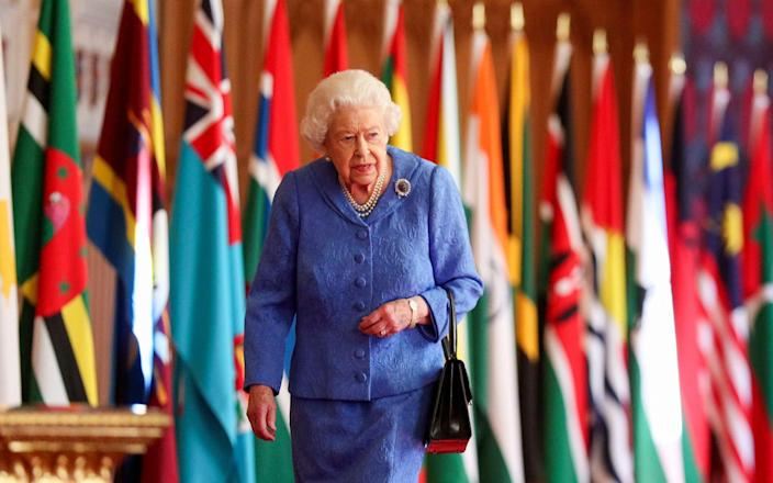 The Queen walks past Commonwealth flags in St George's Hall at Windsor Castle - PA