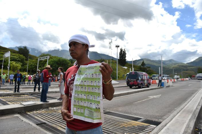 A man shows the pictures of 43 missing students during a protest at the tollbooth on the highway between Acapulco and Mexico DF on October 5, 2014 (AFP Photo/Yuri Cortez )