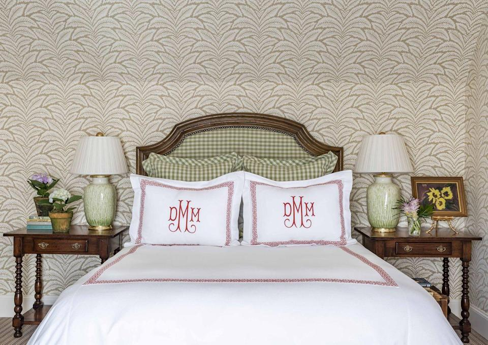 """<p>Sometimes a degree or two """"off"""" of traditional color pairings helps add cadence and rhythm to pattern combinations. For example, instead of classic red and green, this bedroom is more of a raspberry and kiwi combination. Pottery lamps (by <a href=""""https://www.bradburnhome.com/collections/table-lamps"""" rel=""""nofollow noopener"""" target=""""_blank"""" data-ylk=""""slk:Bradburn"""" class=""""link rapid-noclick-resp"""">Bradburn</a>) pick up on the green hue in the checks, while warm brown antique side tables add earthiness.<br></p>"""