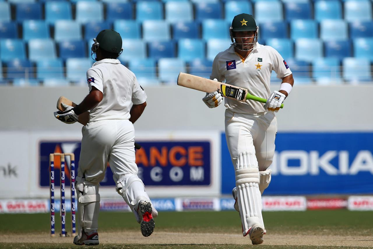 Pakistani batsman Misbah Ul Haq (R) and his teammate Asad Shafiq run between wickets during the fourth day of the second Test cricket match between Pakistan and South Africa in Dubai on October 26, 2013. AFP PHOTO/MARWAN NAAMANI        (Photo credit should read MARWAN NAAMANI/AFP/Getty Images)