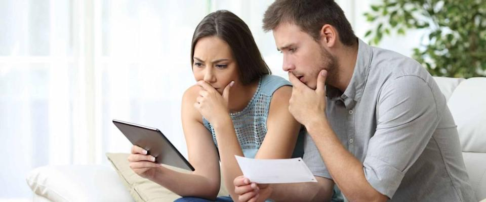 Concerned looking couple sit on couch, looking at tablet and pieces of paper