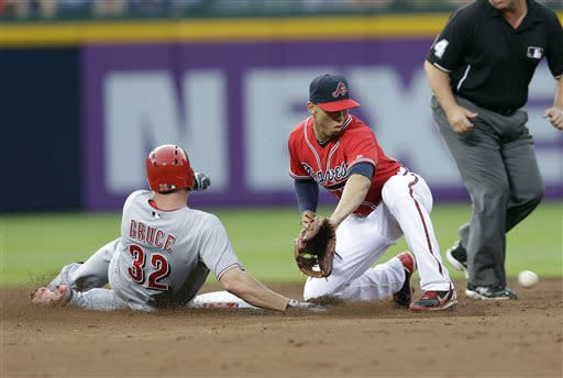 Cincinnati Reds' Jay Bruce (32) is safe at second with a double as Atlanta Braves shortstop Andrelton Simmons, center, handles the late throw in the third inning of a baseball game on Friday, July 12, 2013, in Atlanta. (AP Photo/John Bazemore)