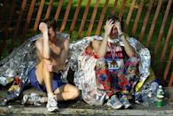 <p>Exhausted runners rest at the end of the New York City Marathon in Central Park November 2, 2003 in New York City. Over 30,000 runners from all over the world participated in the annual race, one of most famous marathons in the world. (Photo by Chris Hondros/Getty Images) </p>